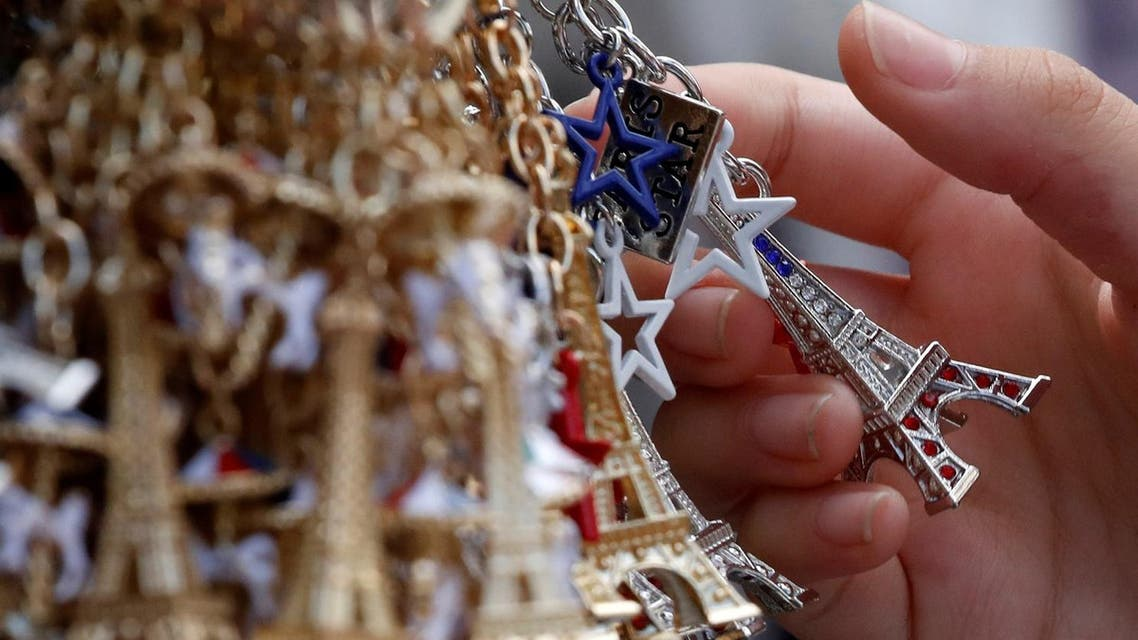 Tourists look at Eiffel Tower keychains displayed in a souvenir shop in Paris, France August 2, 2017. (Reuters)