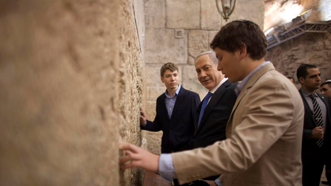 Israeli Prime Minister Benjamin Netanyahu, center, prays with his sons Yair, background, and Avner, right, at the Western Wall, the holiest site where Jews can pray, in Jerusalem's Old City. (AP)