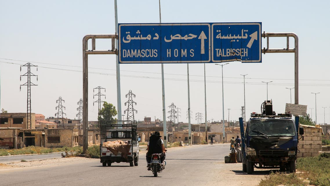 """A picture taken on August 3, 2017 shows vehicles driving past a roadsign that says """"Talbiseh"""" in the eponymous central Syrian rebel-held town, north of Homs, along the highway between the capital Damascus and the central city of Homs. A ceasefire between government forces and rebels went into effect in part of central Syria on August 3, 2017 after Russia struck a deal with the opposition on a safe zone in the northern parts of Homs province.  The truce is the third to be established in Syria, which has been ravaged by six years of civil war that have left more than 300,000 people dead. MAHMOUD TAHA / AFP"""