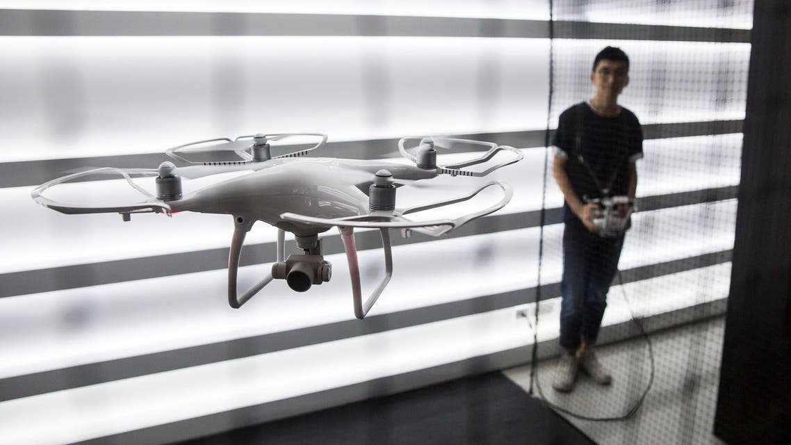 A employee (R) demonstrates an unmanned aerial vehicle (UAV or Drone) during the opening of the DJI flagship store in the Causeway Bay district of Hong Kong on September 24, 2016. DJI is a Chinese technology company founded in 2006 by Frank Wang and makes unmanned aerial vehicles (UVA or Drones) for aerial photography and videography.