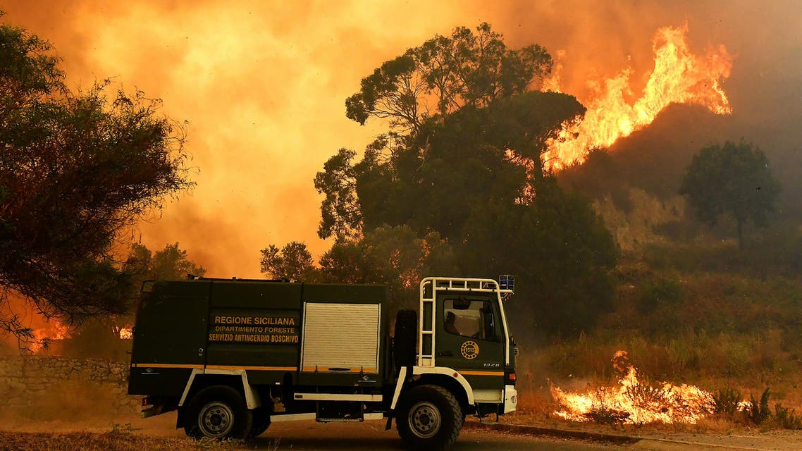 This photograph taken on July 10, 2017, shows a fire rescue vehicle in the Annunziata district of Messina as a fire rages. Across the country Italian firefighters have intervened more than a thousand times in the last days to fight brush or scrub fires. GIOVANNI ISOLINO / AFP