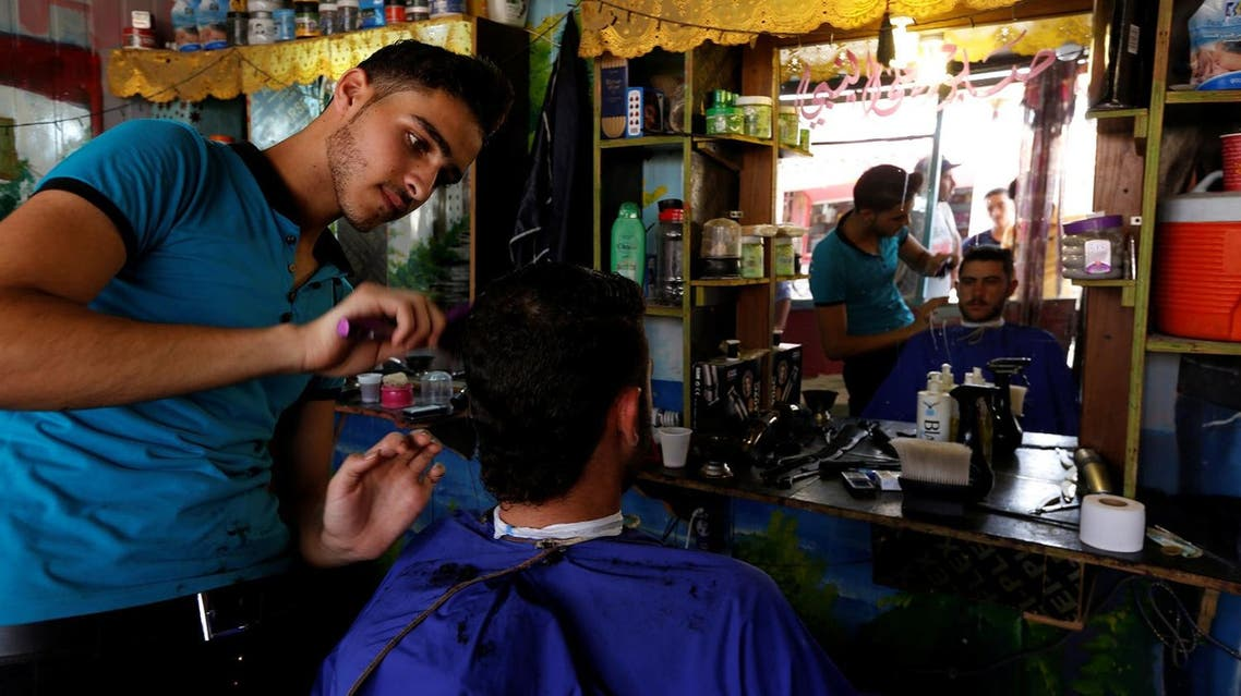 A Syrian barber gives a man a haircut at the main market in Al Zaatari refugee camp outside the city of Mafraq in Jordan. (File photo: Reuters)