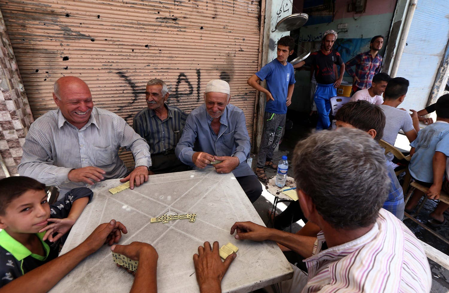 Iraqi men play dominos at a cafe in the old city in west Mosul on July 30, 2017. AFP