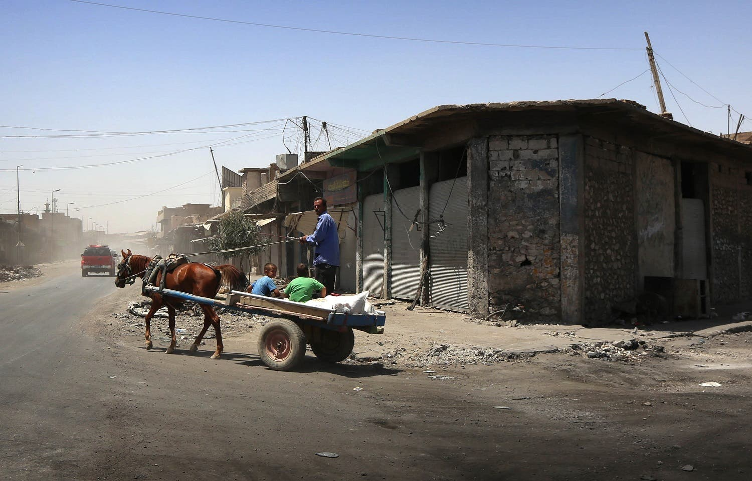 Iraqis ride a cart in western Mosul's old city on July 30, 2017. AFP