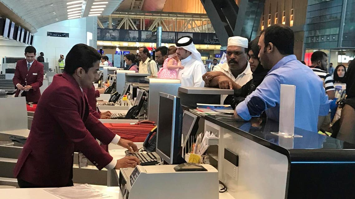In this Monday, June 12, 2017 photo, Qatari and other nationals queue at the check in counters of the Hamad International Airport in Doha, Qatar. An AP videojournalist recounts her struggle to fly back home to Dubia after a diplomatic dispute with Arab Gulf countries saw Qatar, a hub of global air travel, cut off from local flight routes. (AP Photo/Malak Harb)