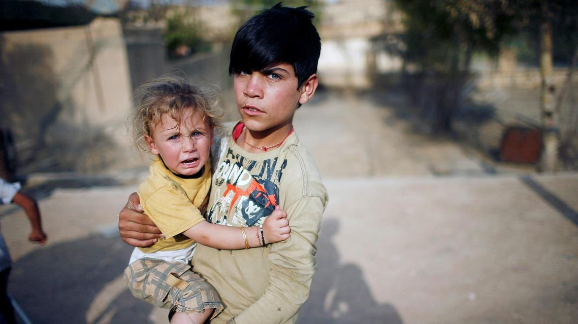 A yazidi boy holds his sister in a playground in Sinjar region. Iraq's Yazidis are marking three years since Islamic State launched what the United Nations said was a genocidal campaign against them, but their ordeal is far from over despite the ouster of the jihadist fighters. (Reuters)