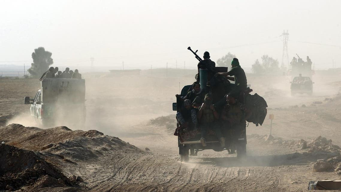 """Shiite fighters from the Popular Mobilization Forces arrive in an area south of Mosul, on October 22, 2016, during an operation to retake the main hub city from the Islamic State (IS) group jihadists. Mosul is the most populous city in the """"caliphate"""" Baghdadi declared in June 2014, and the operation to recapture it is Iraq's largest in years."""