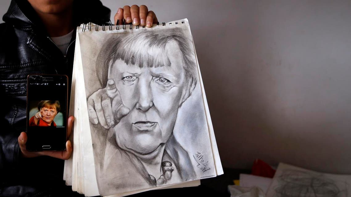 """Farhad Nouri poses with a drawing of German Chancellor Angela Merkel in his room in the """"Krnjaca"""" collective centre near Belgrade, Serbia, Monday, March 13, 2017. A 10-year-old boy from Afghanistan is known as Little Picasso among migrants in a Serbia asylum camp because of his artistic talent. Nouri, his parents and two younger brothers hope to move to Switzerland or the United States, but have been stuck in the Balkan country for months unable to cross the heavily guarded borders of the European Union. (AP Photo/Darko Vojinovic)"""
