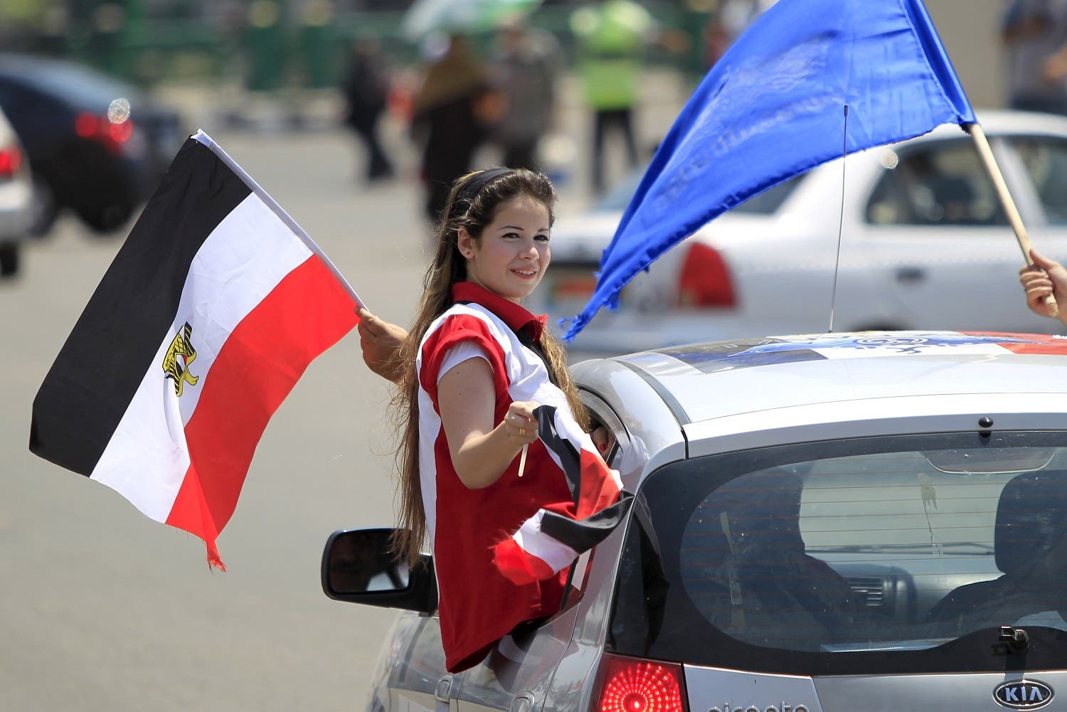 A girl carries a national flag while riding in a car as people gather in Tahrir square to celebrate an extension of the Suez Canal, in Cairo, Egypt, August 6, 2015. (Reuters)
