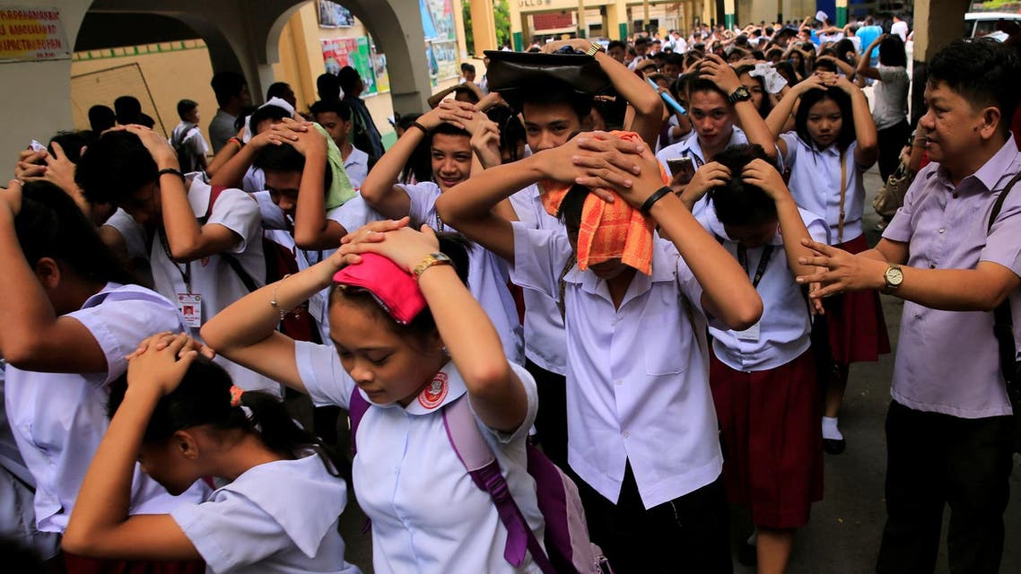 Students use their hands to cover their heads as they evacuate their school premises after an earthquake hit the northern island of Luzon and was felt in the Metro Manila. (Reuters)