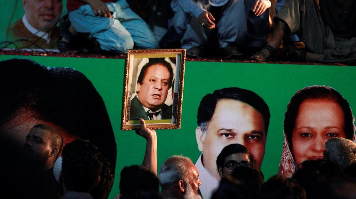 A supporter of former Pakistani prime minister Nawaz Sharif holds his picture as he waits for his convoy to pass through in Rawalpindi, Pakistan, on August 10, 2017. (Reuters)