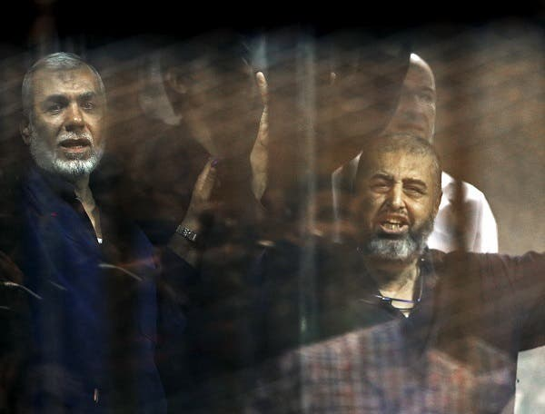 Muslim Brotherhood members gesture behind bars after their verdict at a court on the outskirts of Cairo, Egypt on June 16, 2015. (Reuters)