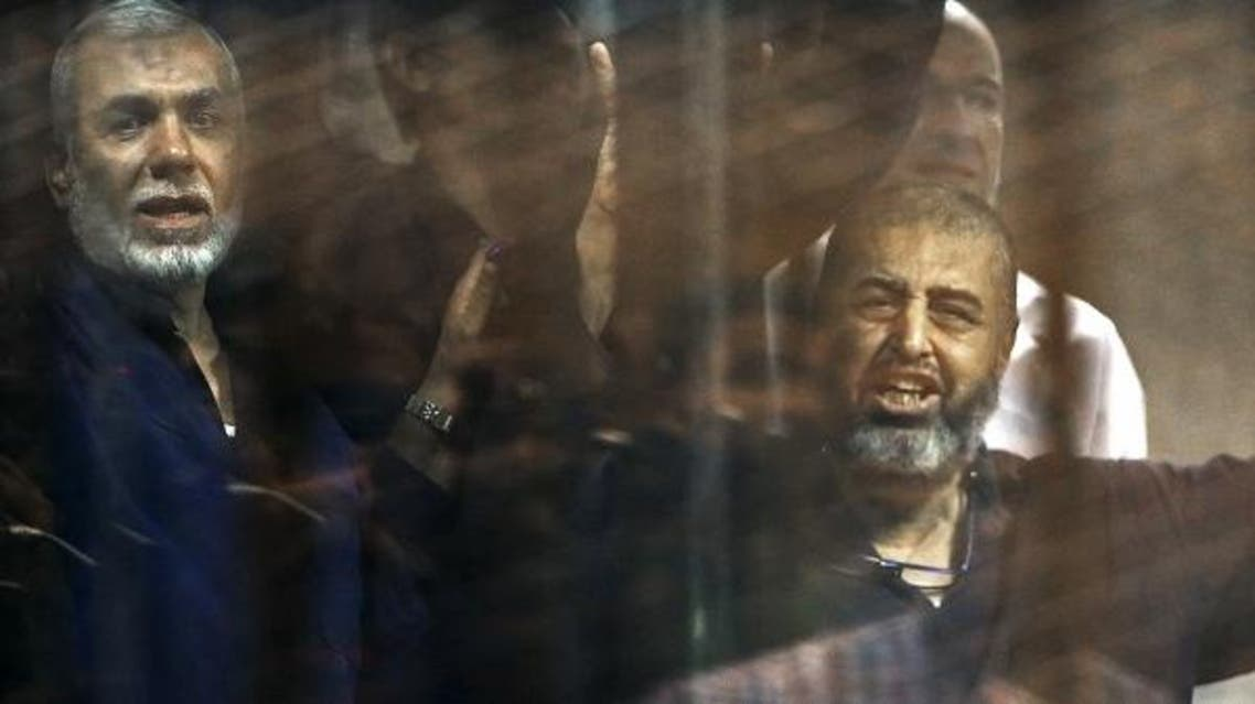 Muslim Brotherhood members gesture behind bars after their verdict at a court on the outskirts of Cairo, Egypt June 16, 2015. (Reuters)