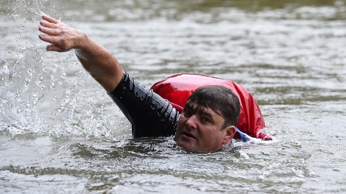 Benjamin David swims from his home to his workplace along the Isar River in Munich, Germany, August 10, 2017. REUTERS/Andreas Gebert