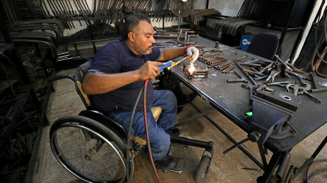 A disabled Egyptian man works in a workshop that manufactures products for the poor disabled in Cairo, Egypt August 8, 2017. (Reuters)