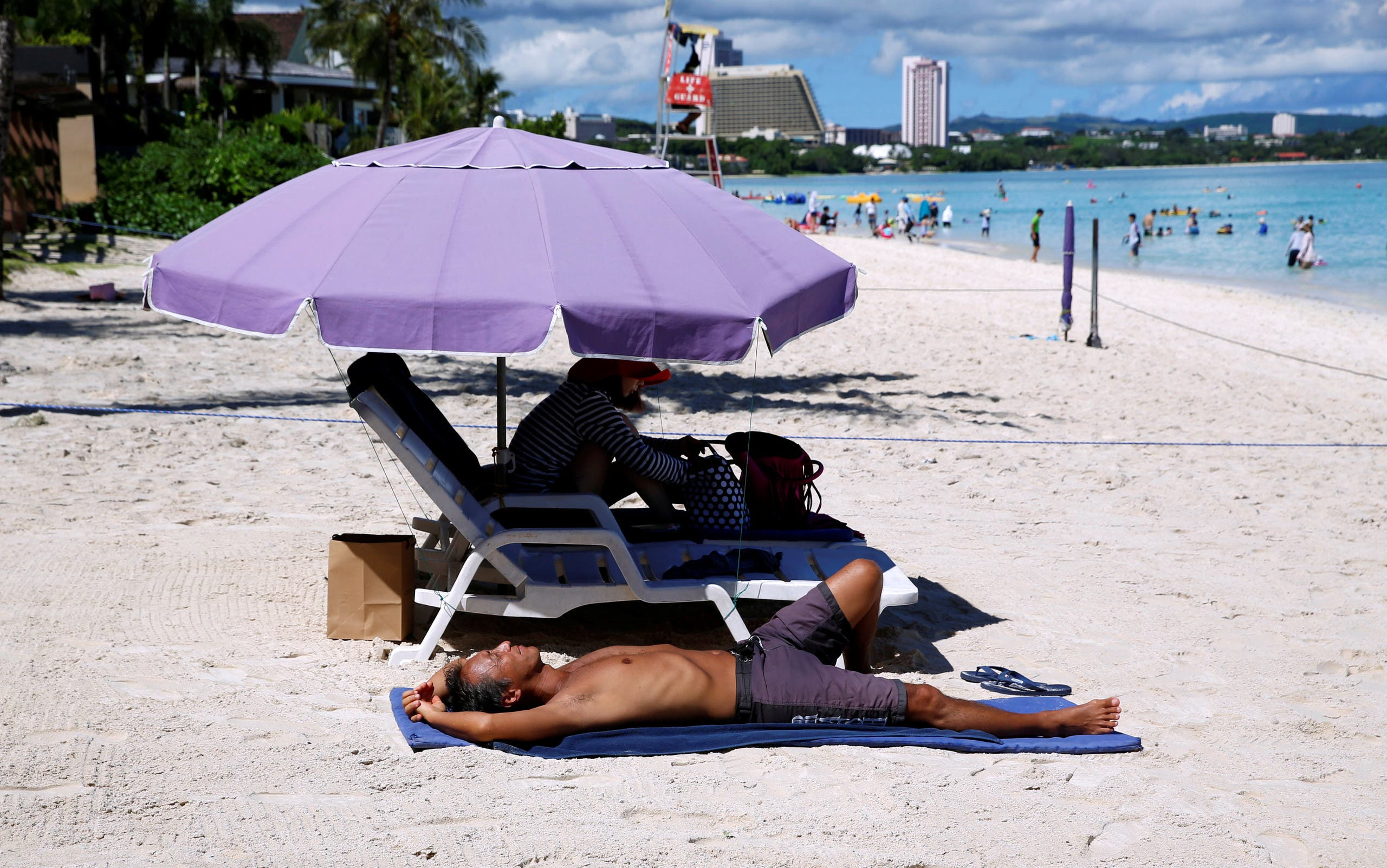 Tourists enjoy the beach in the Tumon tourist district on the island of Guam, a US Pacific Territory, on August 12, 2017. (Reuters)
