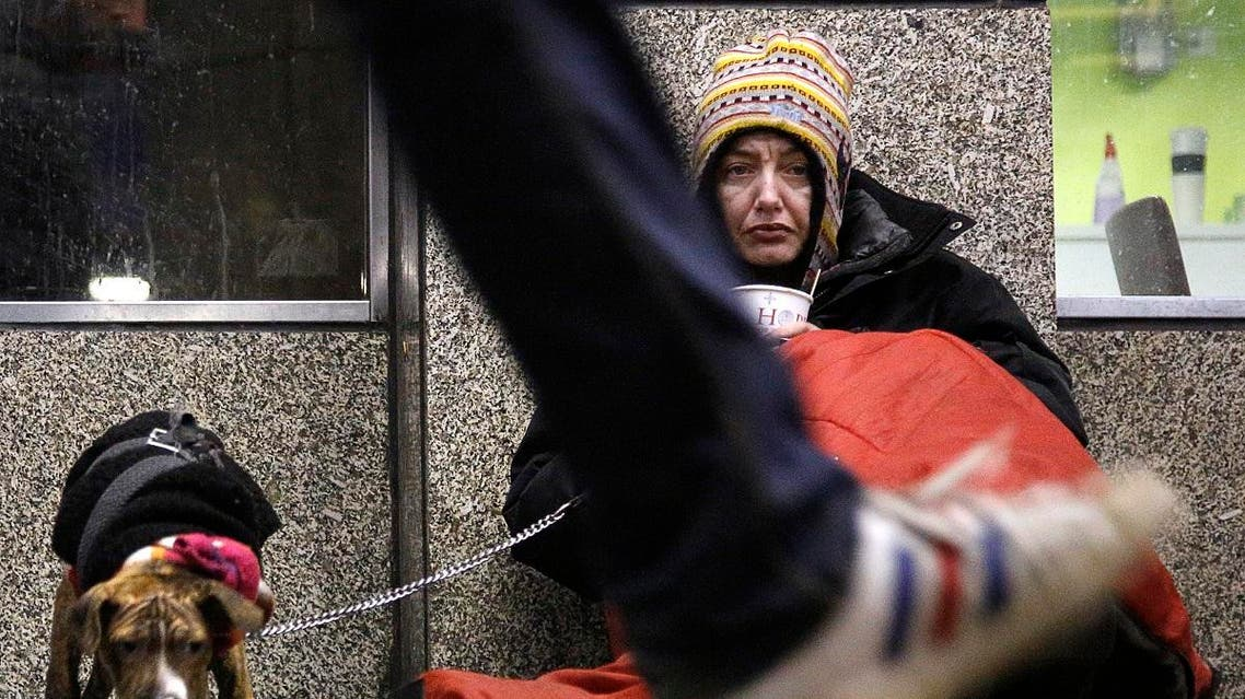 Dawn, a homeless woman from north Wales, sits huddled under a sleeping bag next to her dog Casper in a shopping arcade near the Victoria rail station in central London December 14, 2012. (Reuters)