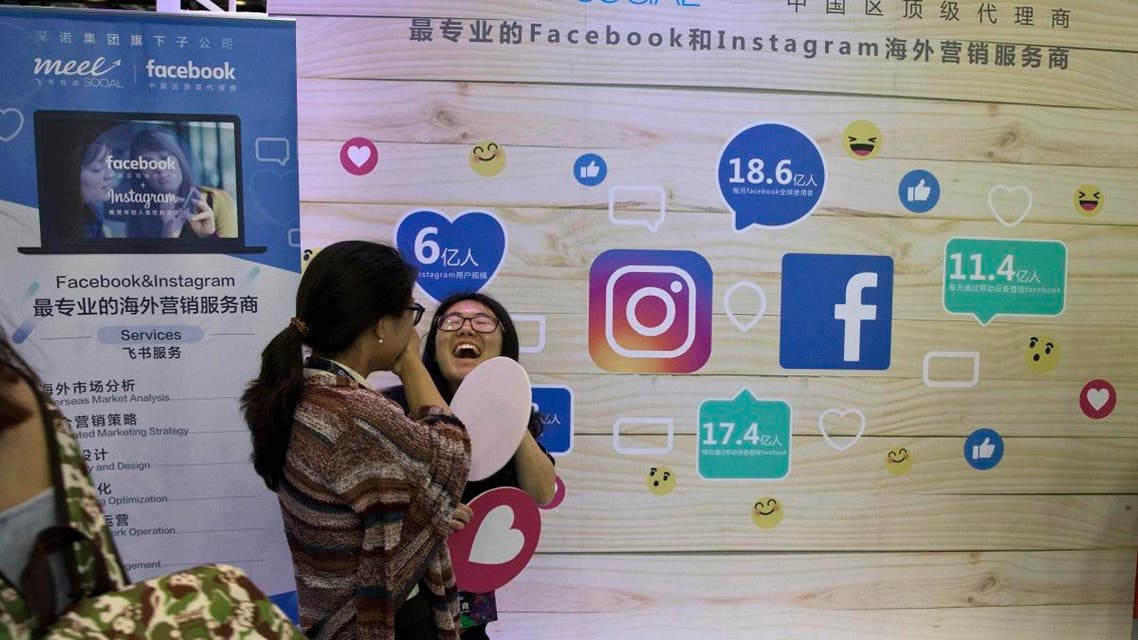 In this Friday, April 28, 2017, photo, a woman reacts near a booth promoting overseas marketing services on Facebook and instagram which are banned in China during an internet conference in Beijing. (AP)