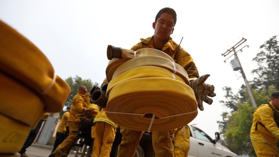 رجل إطفاء يقوم بإنزال مدافع المياه أثناء مكافحة حريق في كاليفورنيا في 19 يوليو تموز 2017