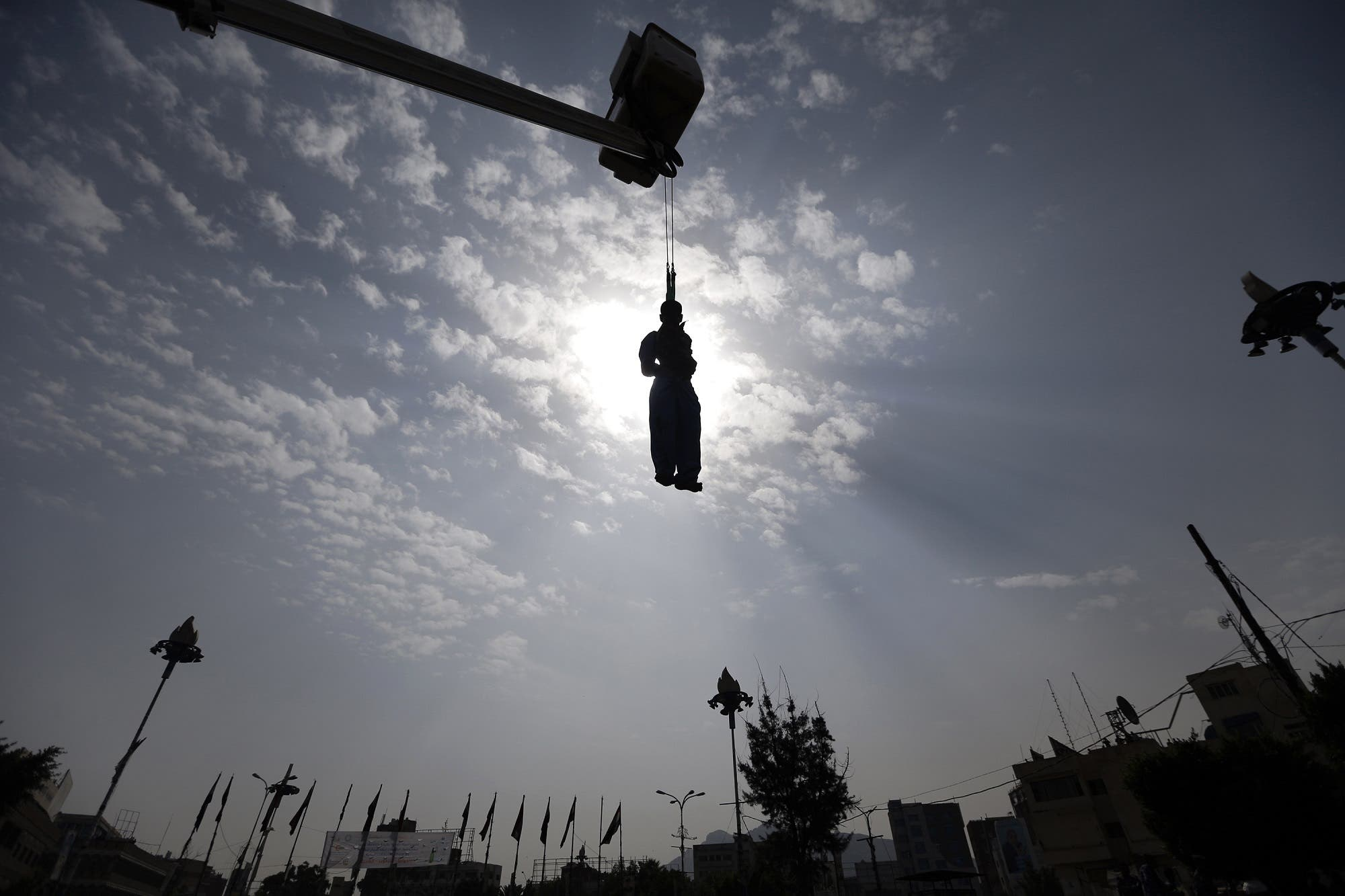 The body of Yemeni Hussein al-Saket, 22, is seen hanging after being executed by security forces for raping and murdering a four-year-old girl, in the capital Sanaa's Tahrir Square, on August 14, 2017. (AFP)