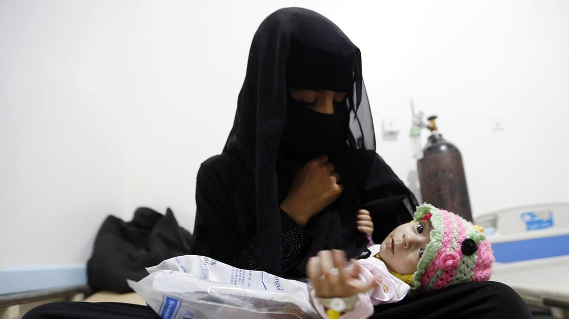Yemeni woman holds her child, who is suspected of being infected with cholera, at a makeshift hospital in the capital Sanaa. (AFP)