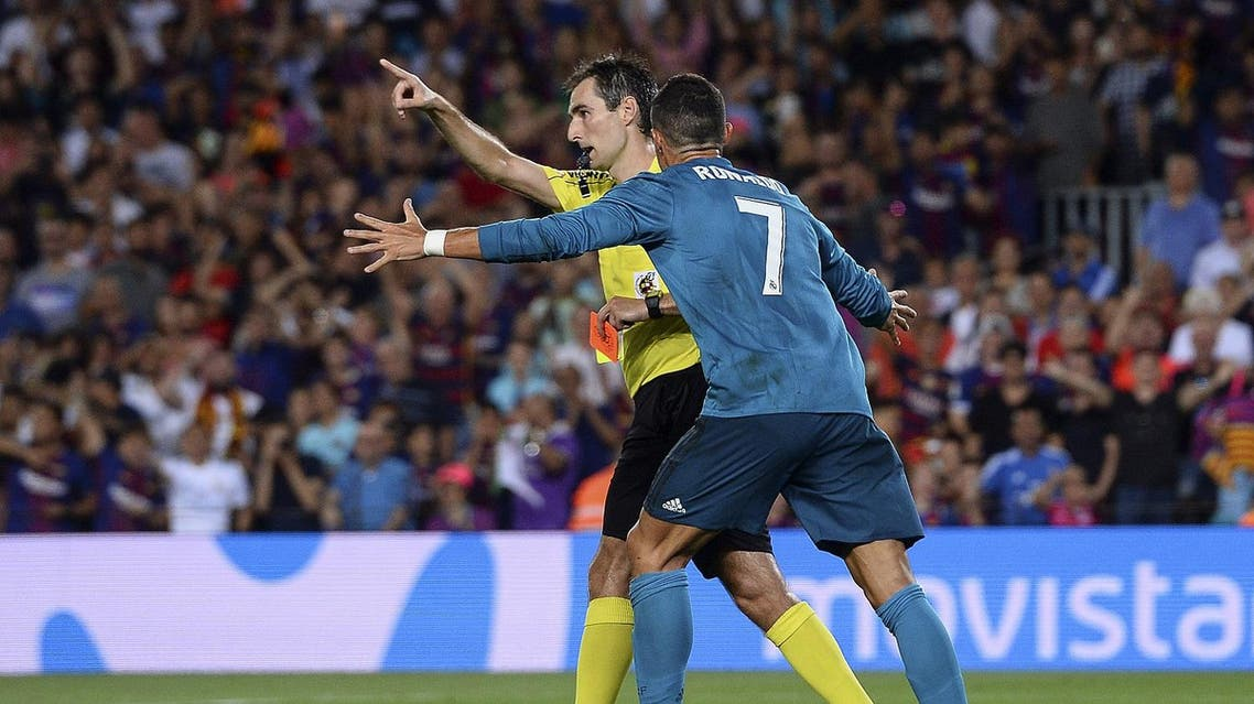 Real Madrid's Portuguese forward Cristiano Ronaldo (R) gestures after receiving a red card by referee Ricardo de Burgos Bengoetxea during the first leg of the Spanish Supercup football match between FC Barcelona and Real Madrid CF at the Camp Nou stadium in Barcelona on August 13, 2017. (AFP)