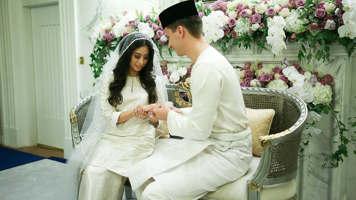 This handout photograph made available on August 14, 2017 by the Royal Press Office shows Dennis Muhammad Abdullah (R) of the Netherlands places the ring on the finger of his bride, Princess Tunku Tun Aminah Sultan Ibrahim (L), the only daughter of the Sultan of Johor, after their wedding at Istana Bukit Serene in Johor Bahru. The daughter of one of Malaysia's most powerful sultans married her Dutch fiance on August 14 in a ceremony steeped in centuries of tradition during a day of lavish celebrations. AFP