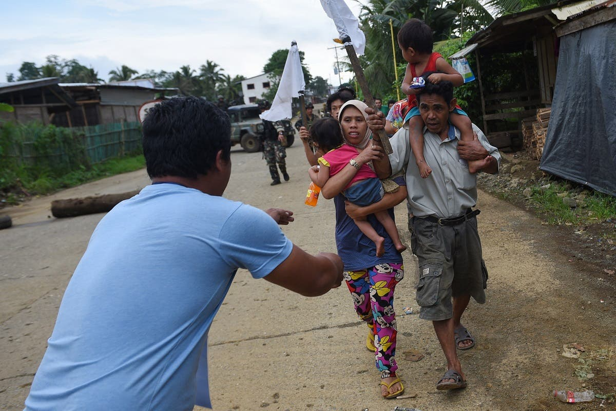 A rescue worker (L) meets residents who were evacuated from their homes after nine days at a village on the outskirts of Marawi on the southern island of Mindanao on May 31, 2017. (AFP)
