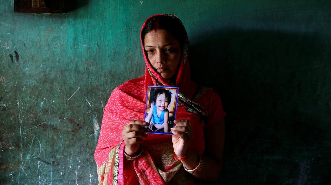 Rinki Singh, 31, holds a photo of her daughter Aarushi, 6, who died in the ICU of the Baba Raghav Das hospital in Gorakhpur, India, on August 14, 2017. (Reuters)