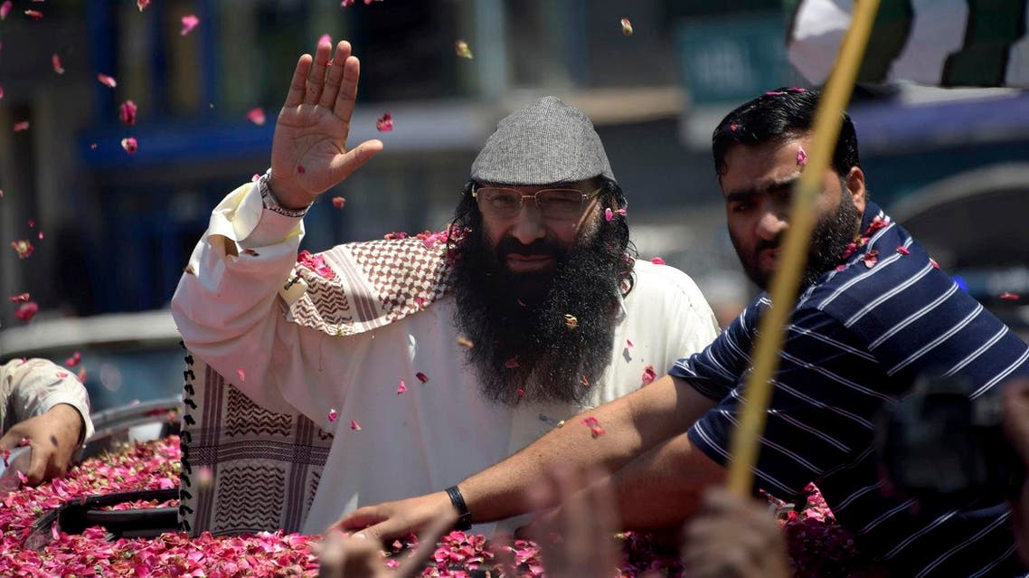Syed Salahuddin (center), top leader of the Hizbul Mujahideen, waves to his supporters upon his arrival for a press conference in Muzaffarabad, the capital of Pakistani controlled Kashmir. (AP)