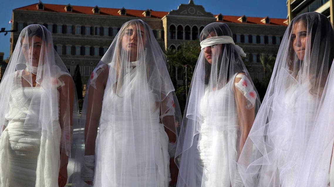 A dozen Lebanese women, dressed as brides in white wedding dresses stained with fake blood and bandaging their eyes, knees and hands stand in front of the government building in downtown Beirut, Lebanon, Tuesday, Dec. 6, 2016. (AP)