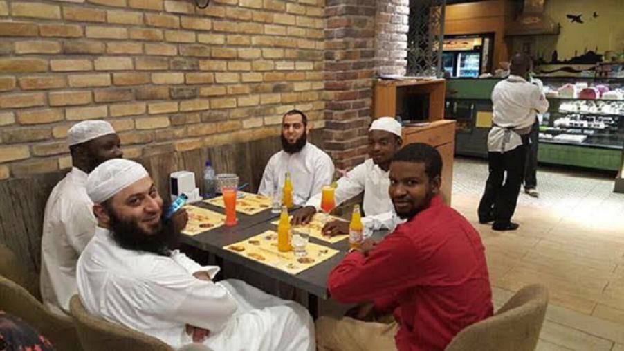 في المطعم قبل الهجوم، الدكتور العلي ملتفتا ينظر الى ملتقط الصورة، ومقابله الى اليسار الشيخ فهد الحسيني
