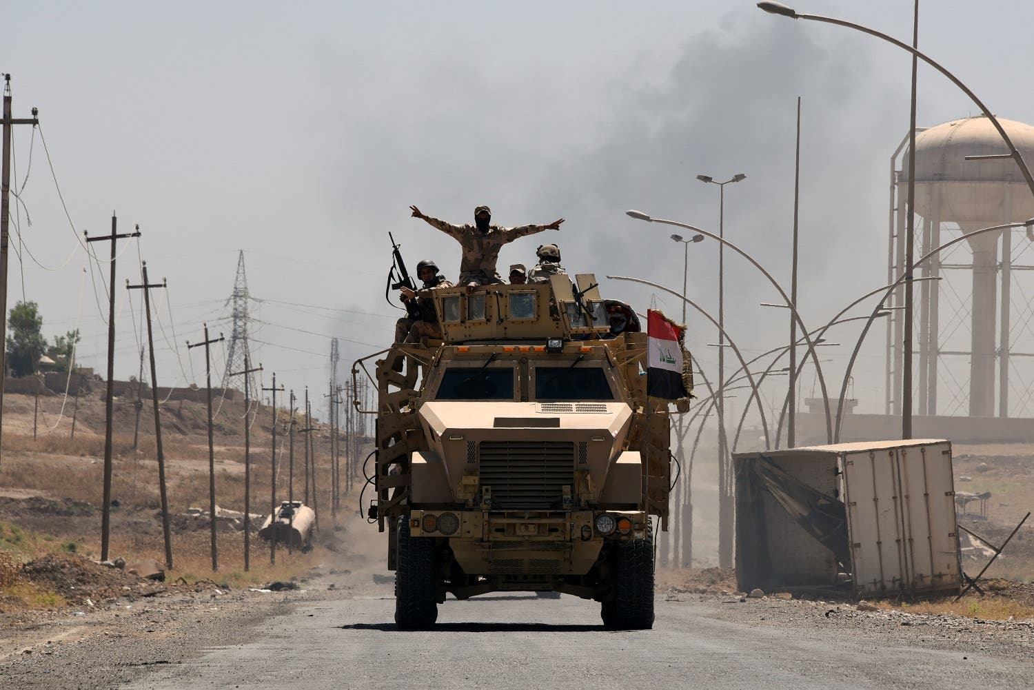 Iraqi government forces drive on a road leading to Tal Afar on June 9, 2017, during ongoing battles to retake the city from ISIS militants. (AFP)