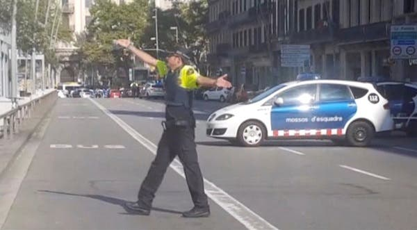a police officer gesturing while walking across a road, after a van crashed into people in the centre of Barcelona, Spain, August 17, 2017. Reuters