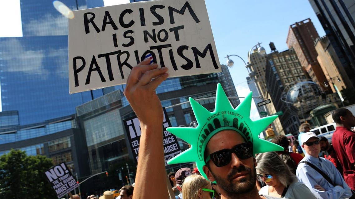 """A protester holds a sign reading """"Racism is not Patriotism"""" at a march against white nationalism in New York City. (Reuters)"""