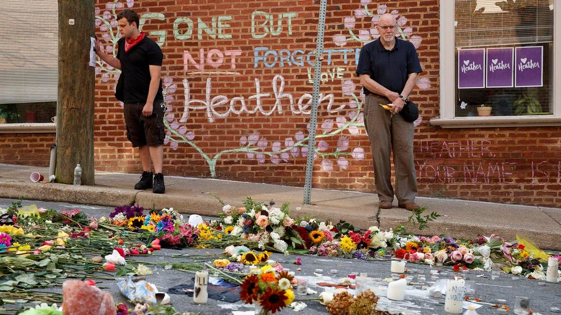 Jason Charter (left), of Washington, stands in Charlottesville at the site where Heather Heyer was killed during a white nationalist rally. (AP)