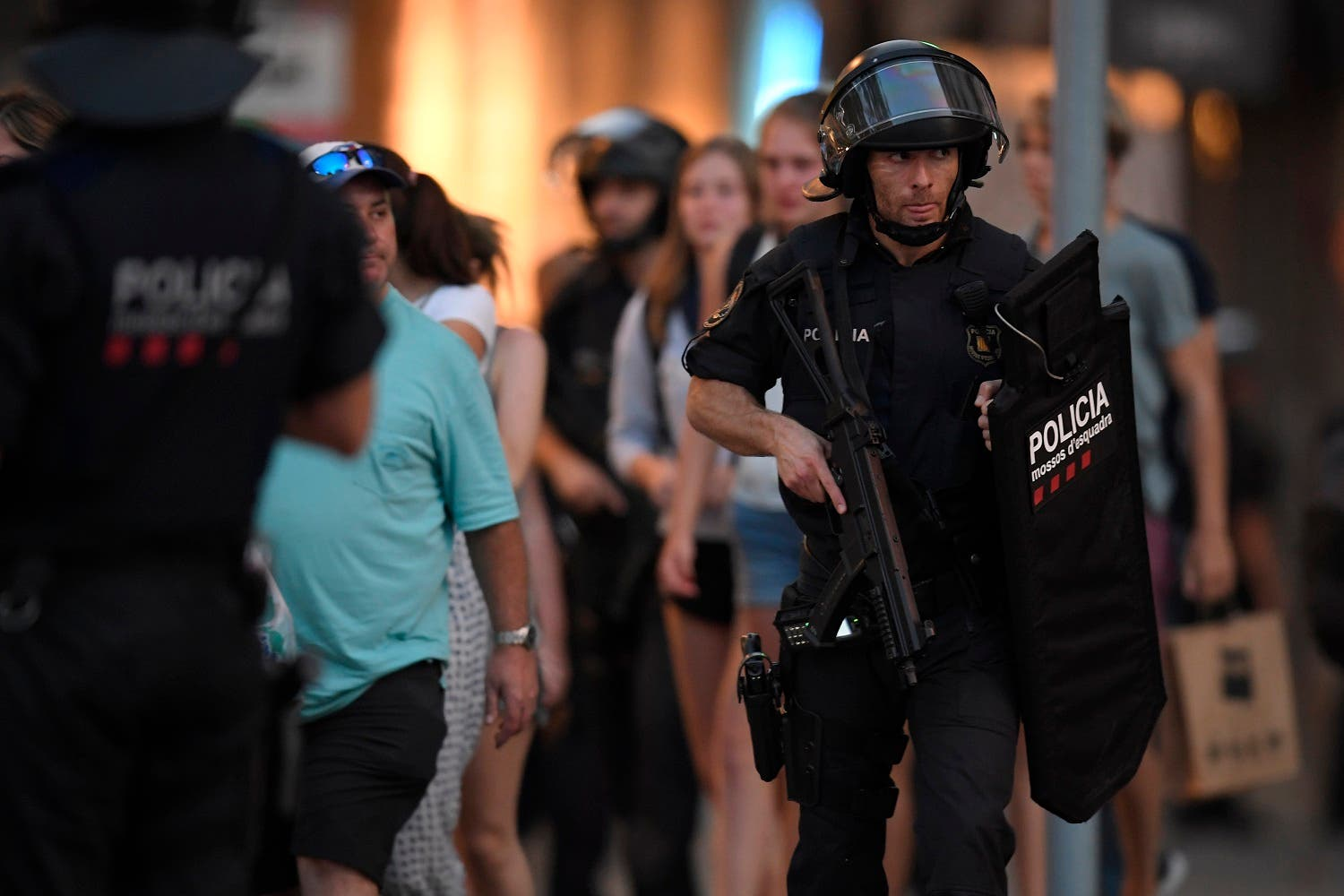 Spanish policemen stand guard in a cordoned off area after a van ploughed into the crowd, killing 13 persons and injuring over 50 on the Rambla in Barcelona on August 17, 2017. A driver deliberately rammed a van into a crowd on Barcelona's most popular street on August 17, 2017 killing at least 13 people before fleeing to a nearby bar, police said. AFP