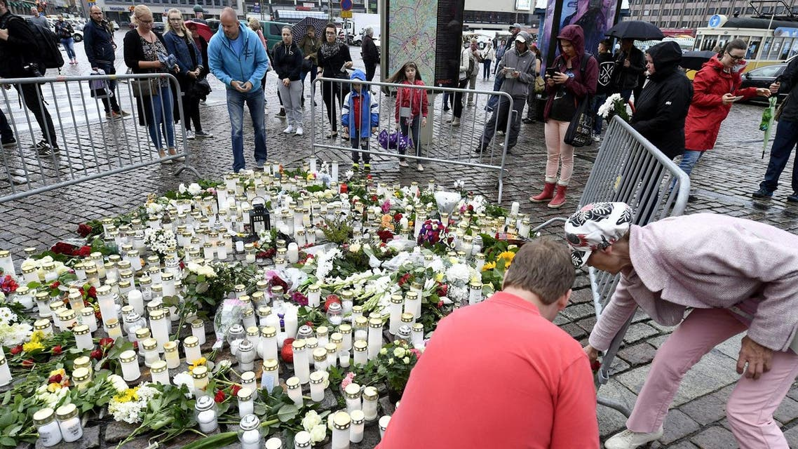 People bring memorial candles and flowers to the Turku Market Square for the victims of Friday's stabbings in Turku. (Reuters)