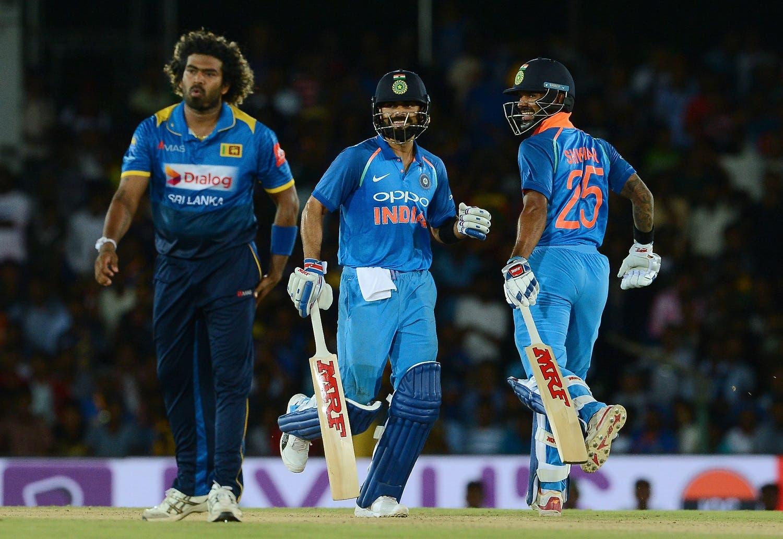 Indian cricket captain Virat Kohli (C) and Shikhar Dhawan run between the wickets during the first One Day International (ODI) cricket match between Sri Lanka and Indian at the Rangiri Dambulla International Cricket Stadium in Dambulla on August 20, 2017. AFP