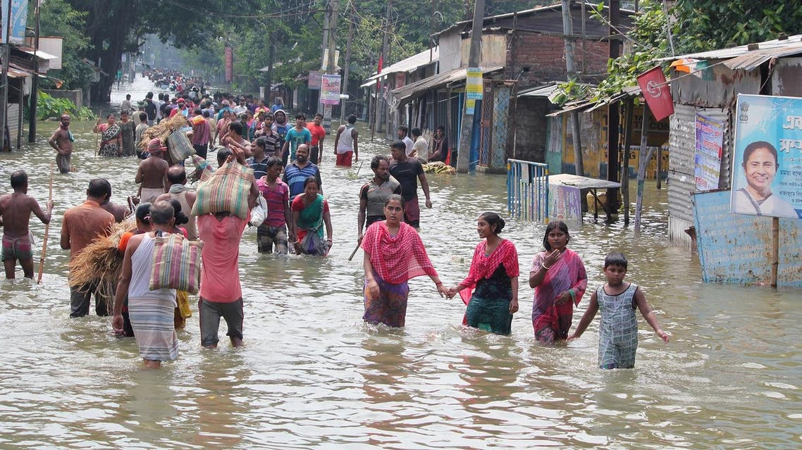 (FILES) This file photo taken on August 17, 2017 shows Indian residents wading through flood waters in Balurghat in West Bengal. Torrential rain across India, Nepal and Bangladesh has killed at least 700 people since August 10, as the annual monsoon swept the north and east of the region. (AFP)