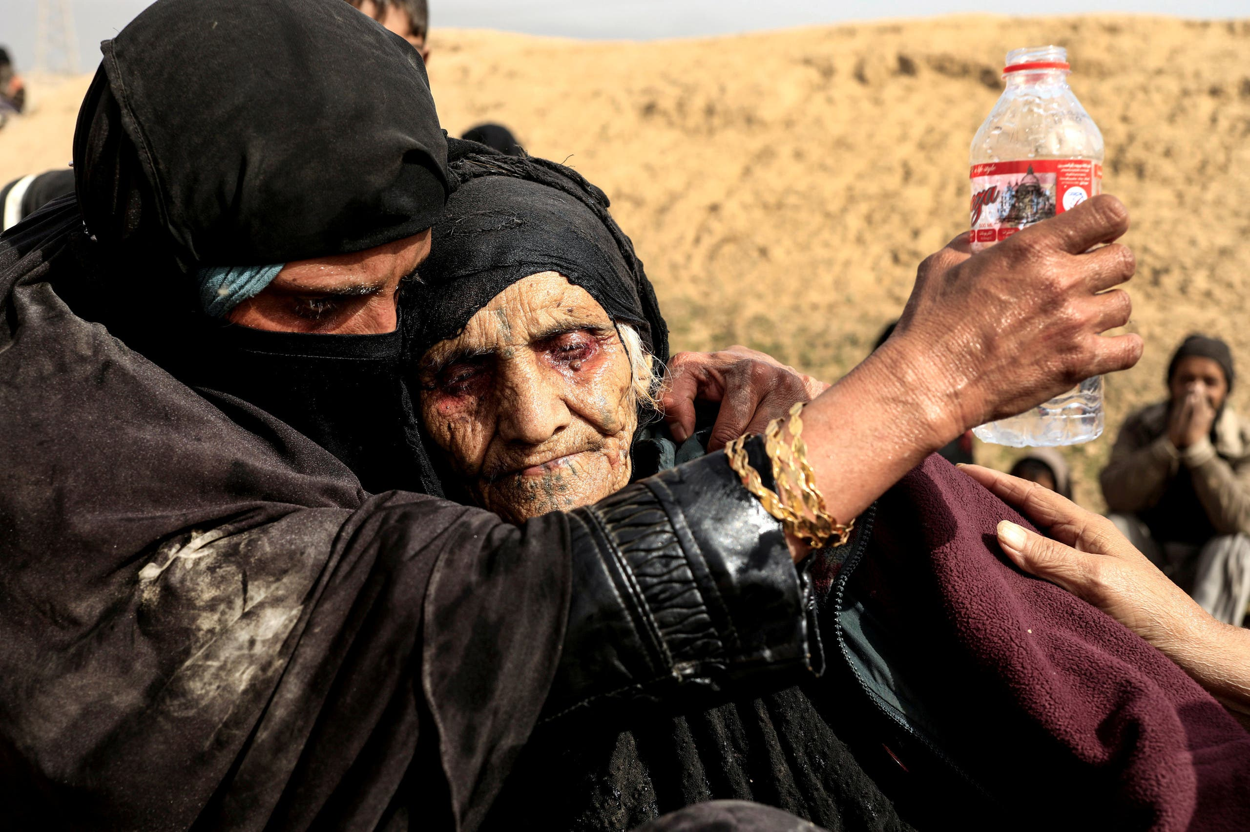 Displaced Iraqi women, who just fled their home, rest in the desert as they wait to be transported while Iraqi forces battle with ISIS militants in western Mosul, Iraq, February 27, 2017. (Reuters)