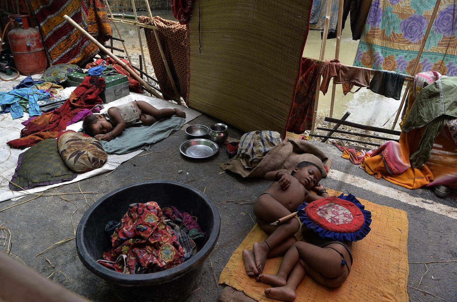 Indian children rest in a makeshift shelter at flood-affected Palsa village in Purnia district in Bihar state on August 18, 2017. At least 221 people have died and more than 1.5 million have been displaced by monsoon flooding across India, Nepal and Bangladesh, officials said August 15, as rescuers scoured submerged villages for the missing. (AFP)