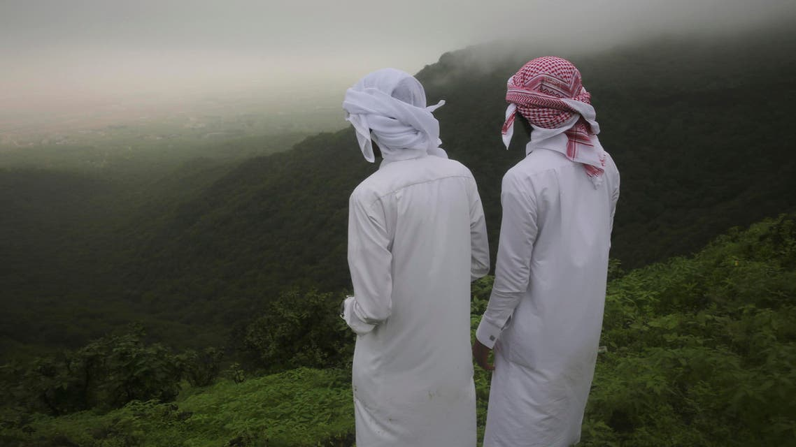 Two Saudi teenage brothers peer out off a cliff in the fog-covered Jabal Ayoub mountains north of Salalah in southern Oman during the annual summer monsoon on Wed. August 2, 2017. (AP)
