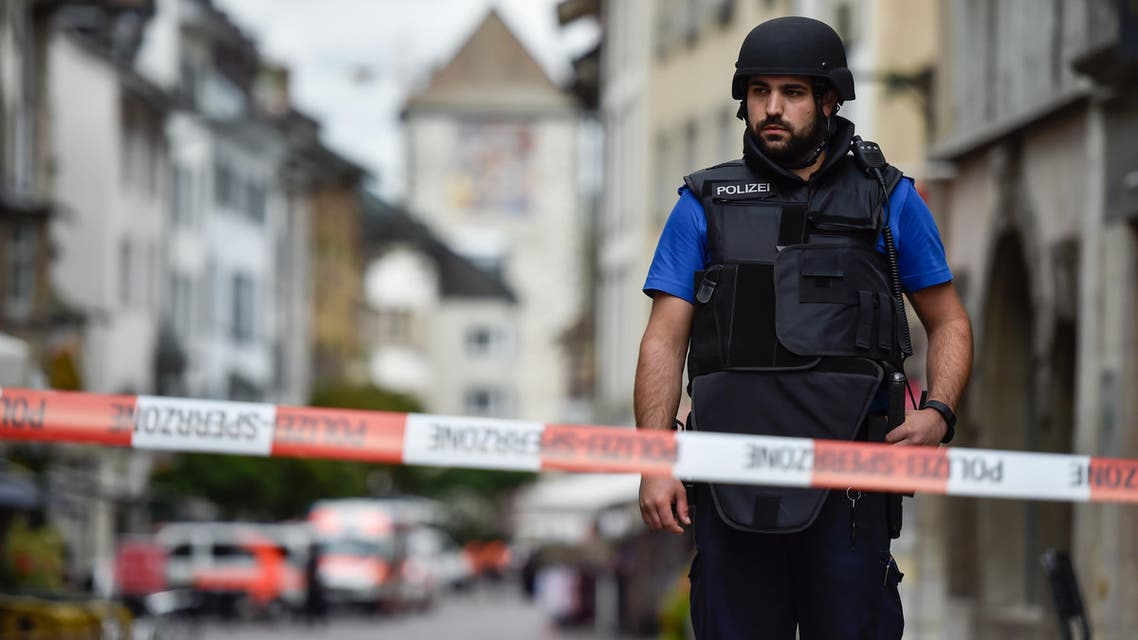 A Swiss policeman is seen standing guard behind a police cordon in the old quarter of Schaffhausen, northern Switzerland on July 24, 2017, after a man armed with a chainsaw injured at least five people in an attack. AFP