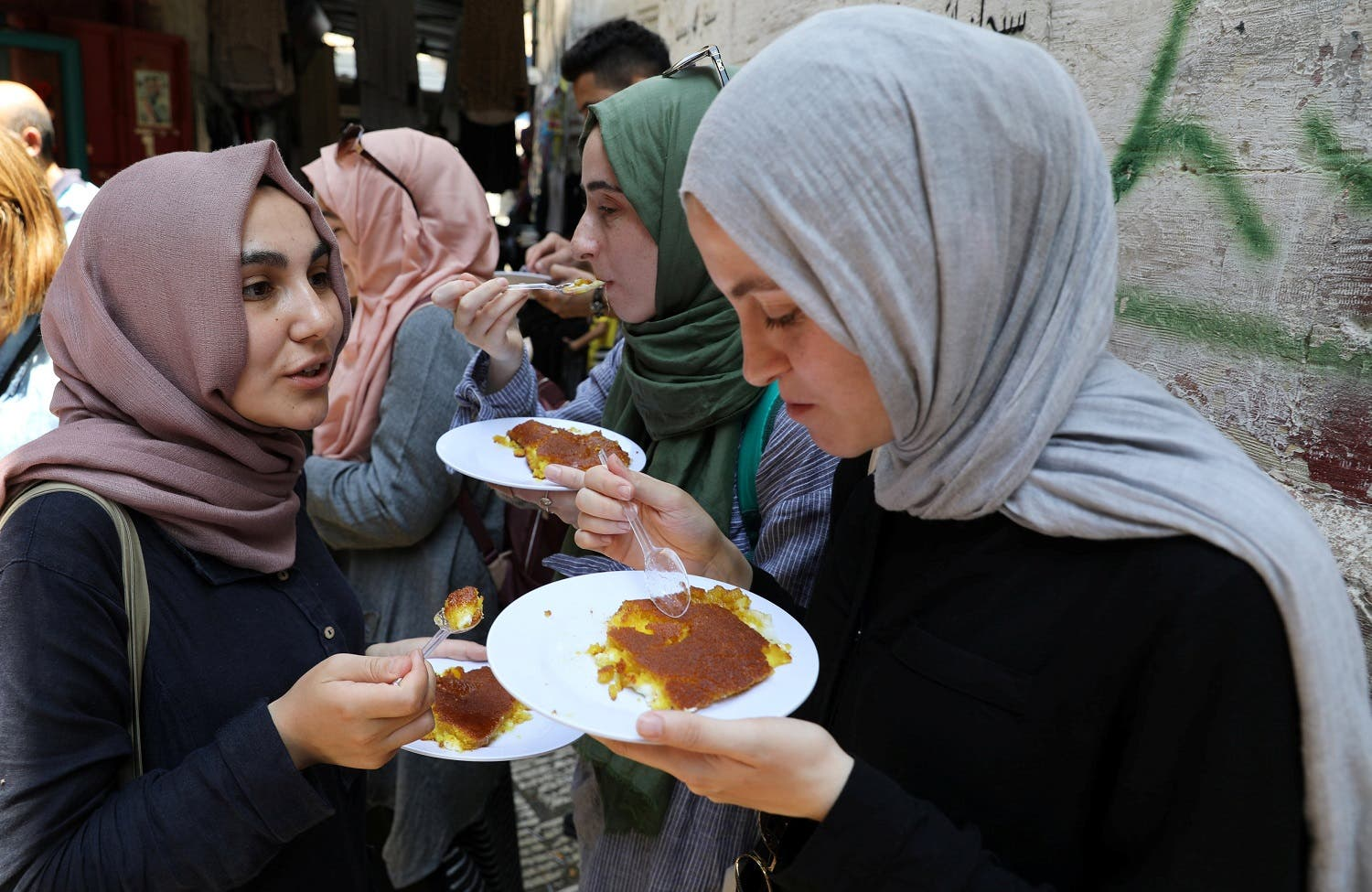 Tourists eat knafa, a sweet semolina and cheese pastry, outside al Aqsa sweet shop in the historic covered market of Nablus in the West Bank August 10, 2017. (Reuters)