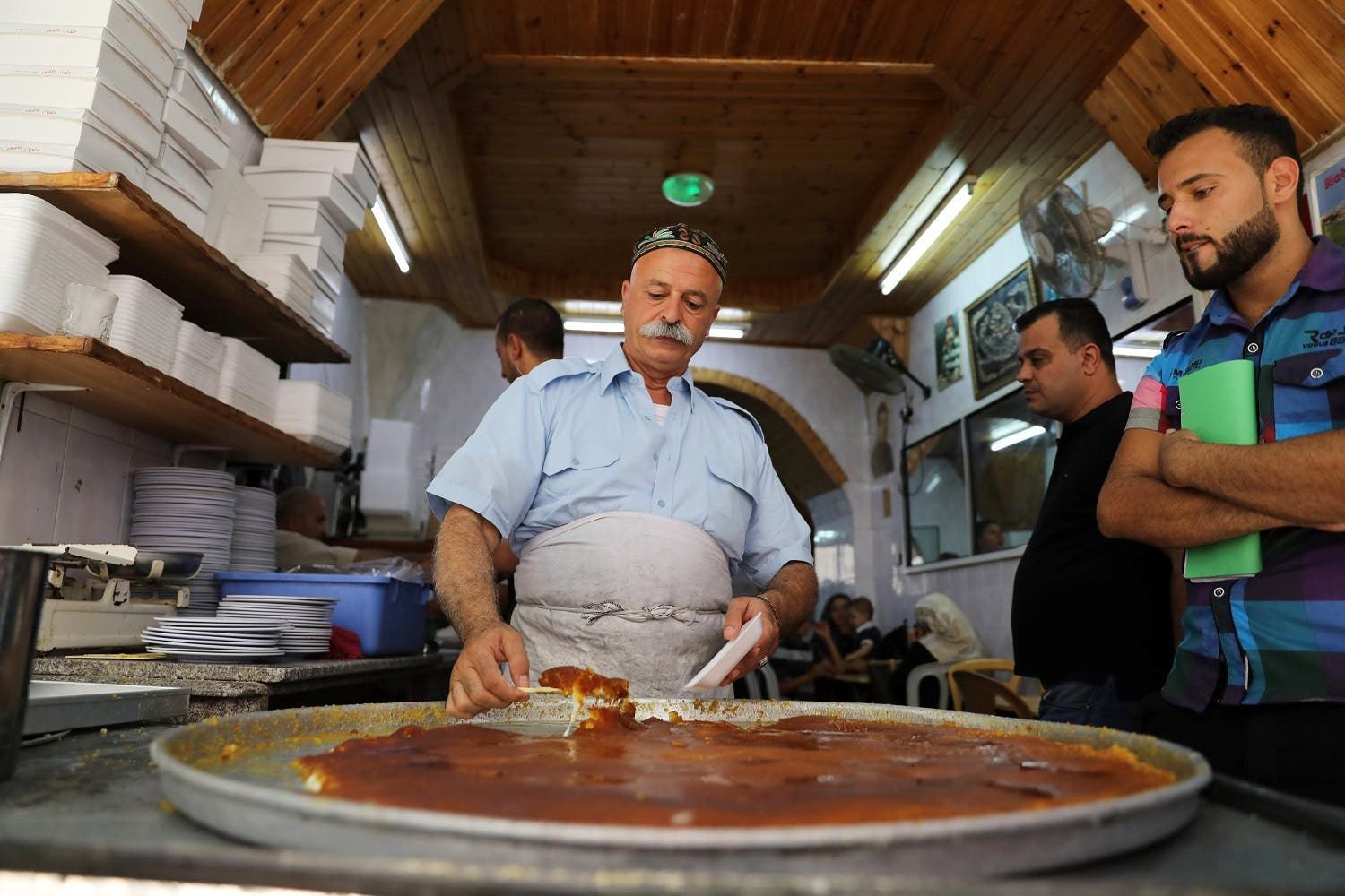 A Palestinian man serves knafa at al Aqsa sweet shop in the historic covered market of Nablus in the West Bank August 10, 2017. (Reuters)
