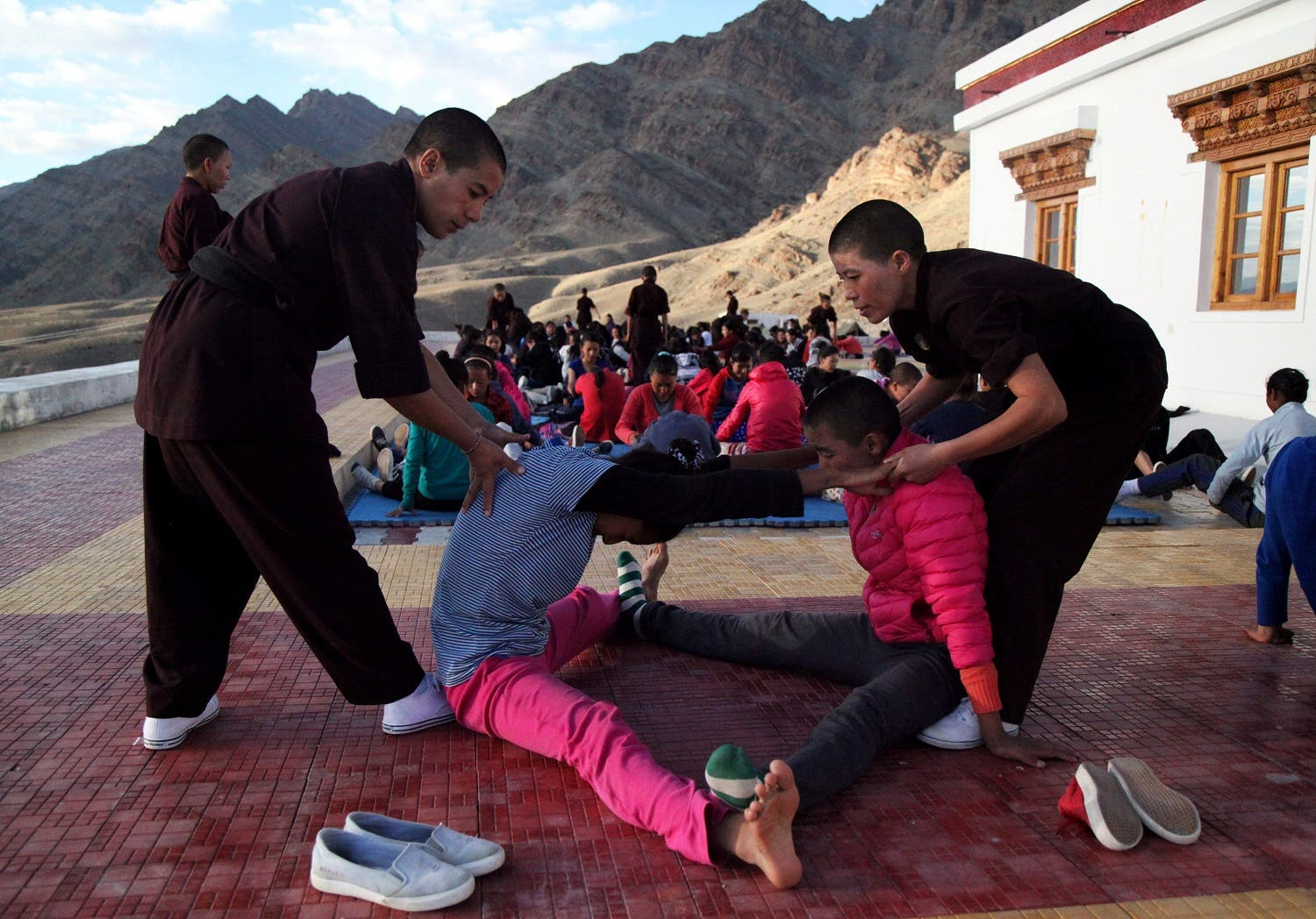 Buddhist nuns help participants stretch during a five-day workshop teaching young women the martial art of Kung Fu, in Hemis region in Ladakh, August 18, 2017. (Reuters)