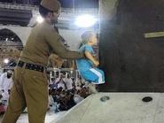 صورة رجل أمن يرفع طفلاً لتقبيل الكعبة تثير الإعجاب