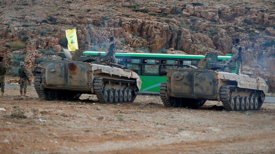 مقاتلون تابعون لحزب الله يرافقون حافلات في جرود عرسال في لبنان
