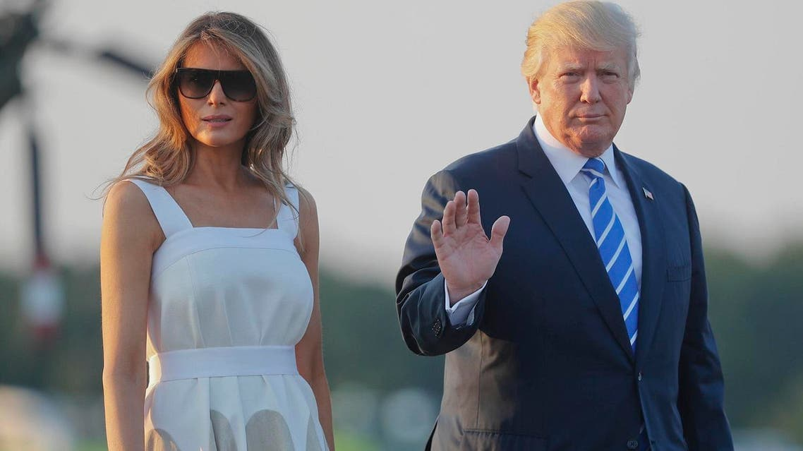 President Donald Trump and first lady Melania Trump walk across the tarmac before boarding Air Force One on August 20, 2017. (AP)